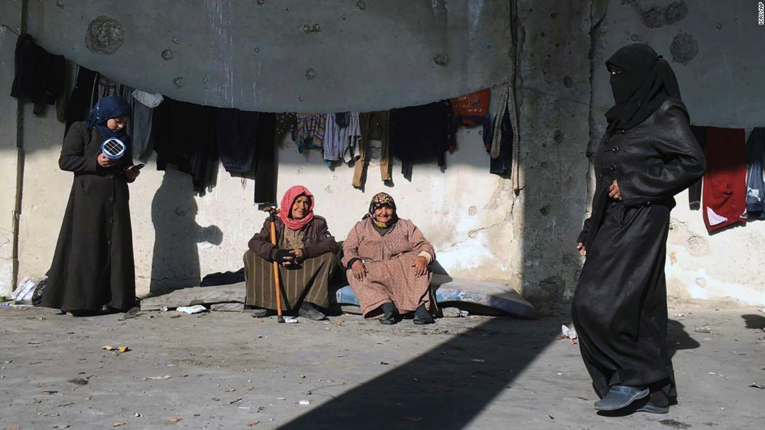 In this handout photo from the International Committee for the Red Cross, women displaced from eastern Aleppo gather at a shelter in the village of Jibreen, south of Aleppo, on December 12.