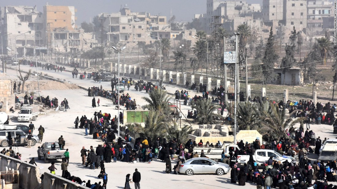 Civilians from eastern Aleppo stream into a government checkpoint at the al-Hawoz street roundabout on Saturday, December 10.