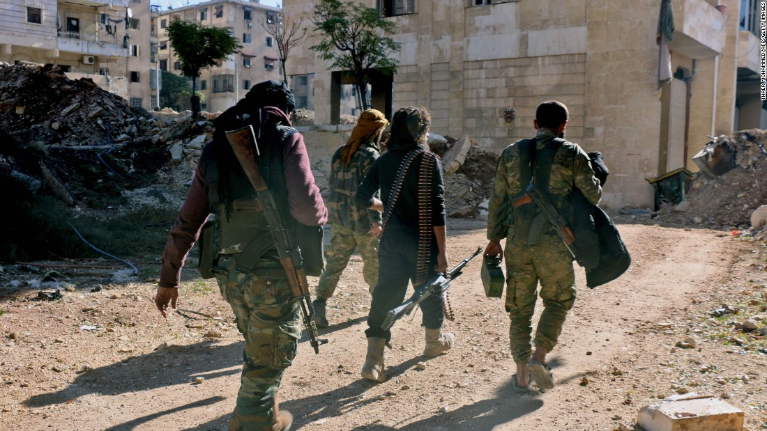 Syrian rebels walk down a street in eastern Aleppo on December 9.