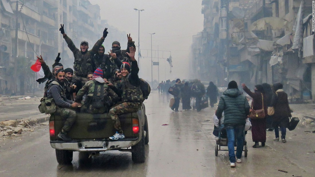 Pro-government fighters wave from a truck as they pass civilians fleeing the Bustan al-Qasr neighborhood on December 13.