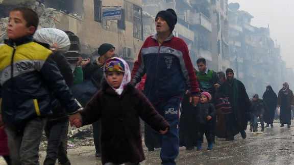Syrian children flee with their families from the Bustan al-Qasr neighborhood in Aleppo on Tuesday.
