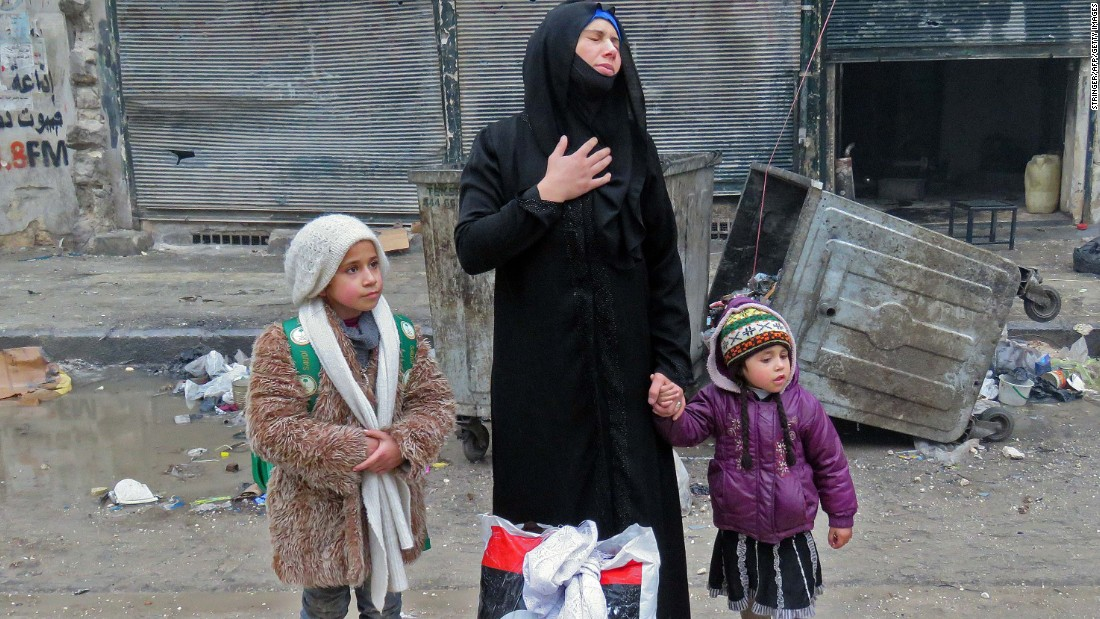 A woman reacts as she evacuates the Bustan al-Qasr neighborhood with her two children on December 13.
