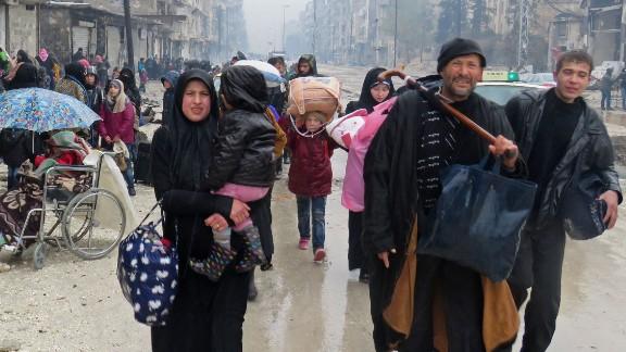 Syrians fleeing the restive Bustan al-Qasr neighbourhood on Tuesday.