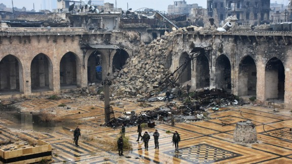 Pro-government forces walk in the ancient Umayyad Mosque after capturing the area on Tuesday, December 13.