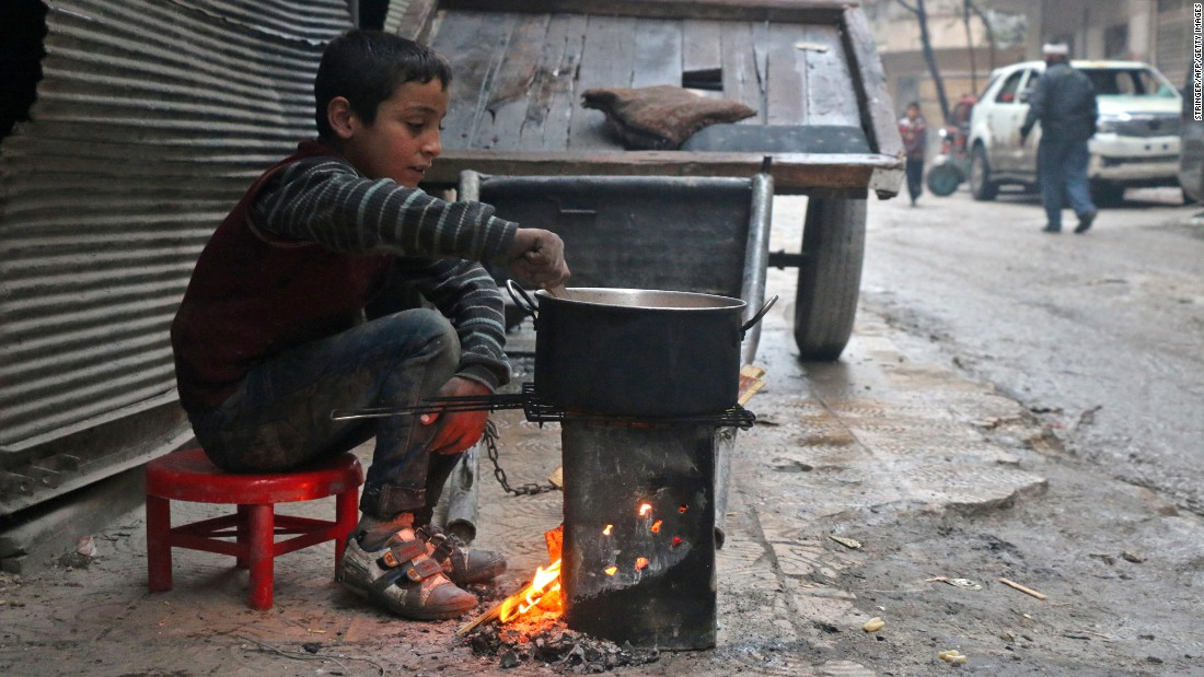 A Syrian child cooks in the street in a rebel-held area of Aleppo on December 13.