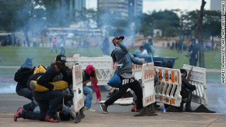 Demonstrators clash with police during a protest in front of the National Congress in Brasilia on December 13, 2016.