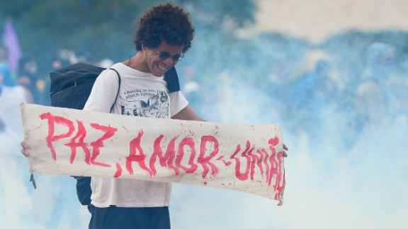 """A demonstrator holds a sign that reads, """"peace, love, and unity,"""" in the midst of a clash between protesters and police outside the National Congress in Brasilia on December 13."""