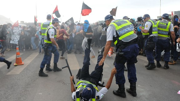 A police officer is knocked down during clashes with demonstrators protesting in front of the National Congress in Brasilia on December 13, 2016.