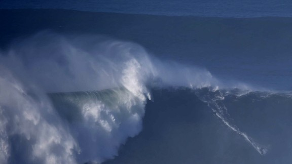 An unidentifyed surfer rides a wave off Praia do Norte in Nazare, central Portugal on December 11, 2014. AFP PHOTO/ FRANCISCO LEONG        (Photo credit should read FRANCISCO LEONG/AFP/Getty Images)