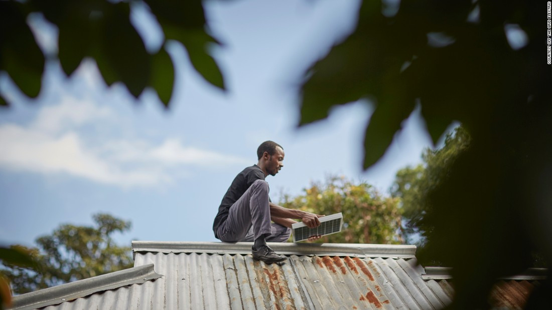 A service officer installs a panel on a new customer's rooftop in Arusha, Tanzania.