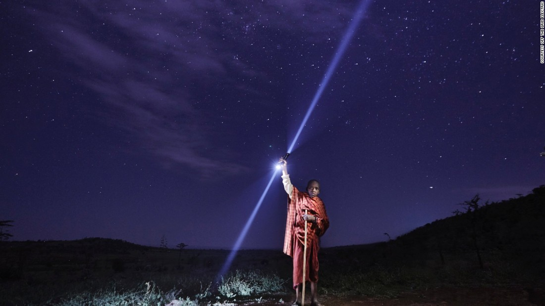 A young Maasai boy brings a solar torch to the field to check on his cattle at night. The torch is part of a program run by Off Grid Electric, a company which aims to bring affordable energy to sub-Saharan Africa.