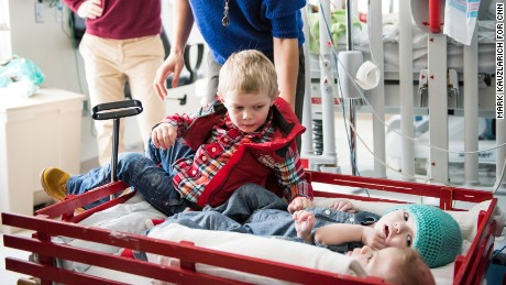 Aza McDonald, 3, crawls into the wagon next to his twin brothers before the party.