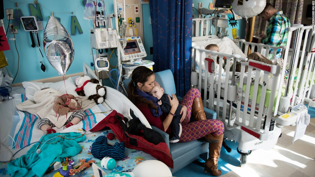 Nicole McDonald holds Anias as his twin brother, Jadon, sleeps in the bed to the left. The twins' older brother, Aza, watches television at the hospital from one of the boys' beds shortly before they left for rehab.
