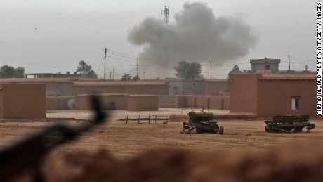 Smoke rises from the village of Shwah, south of the city of Tal Afar on the western outskirts of Mosul, on December 13, 2016, as Shiite fighters from the Hashed al-Shaabi (Popular Mobilisation) paramilitary units advance towards the village during an ongoing operation against Islamic State (IS) group jihadists. Hashed al-Shaabi paramilitary forces said they retook three more villages southwest of Mosul, completing another phase in operations aimed at cutting the jihadists' link to Syria.   / AFP / AHMAD AL-RUBAYE        (Photo credit should read AHMAD AL-RUBAYE/AFP/Getty Images)