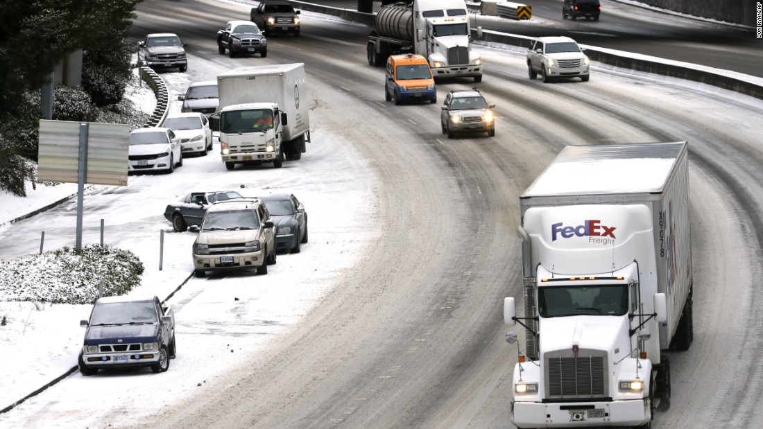 Abandoned cars line the side of Interstate 405 as commuters work their way into Portland, Oregon, on December 15. A winter storm dumped several inches of snow in the area the night before.