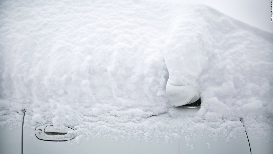 A car is covered in snow in Kalamazoo, Michigan, on Sunday, December 11.