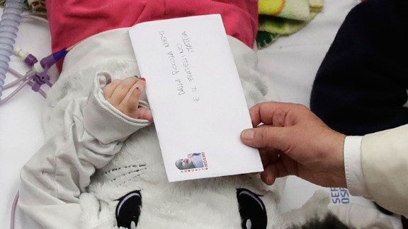 Pope Francis accepts a letter from a child he visited at a pediatric hospital in Rome on Thursday, December 15, 2016.