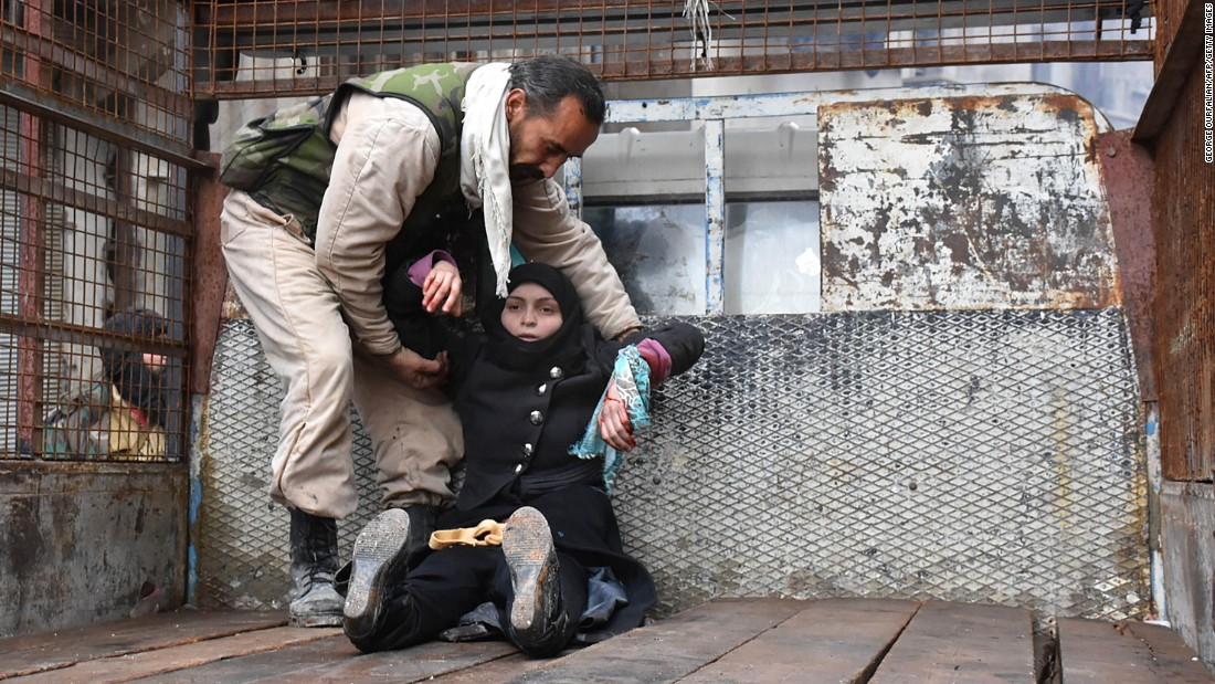 A wounded woman is helped into the bed of a truck on December 14.
