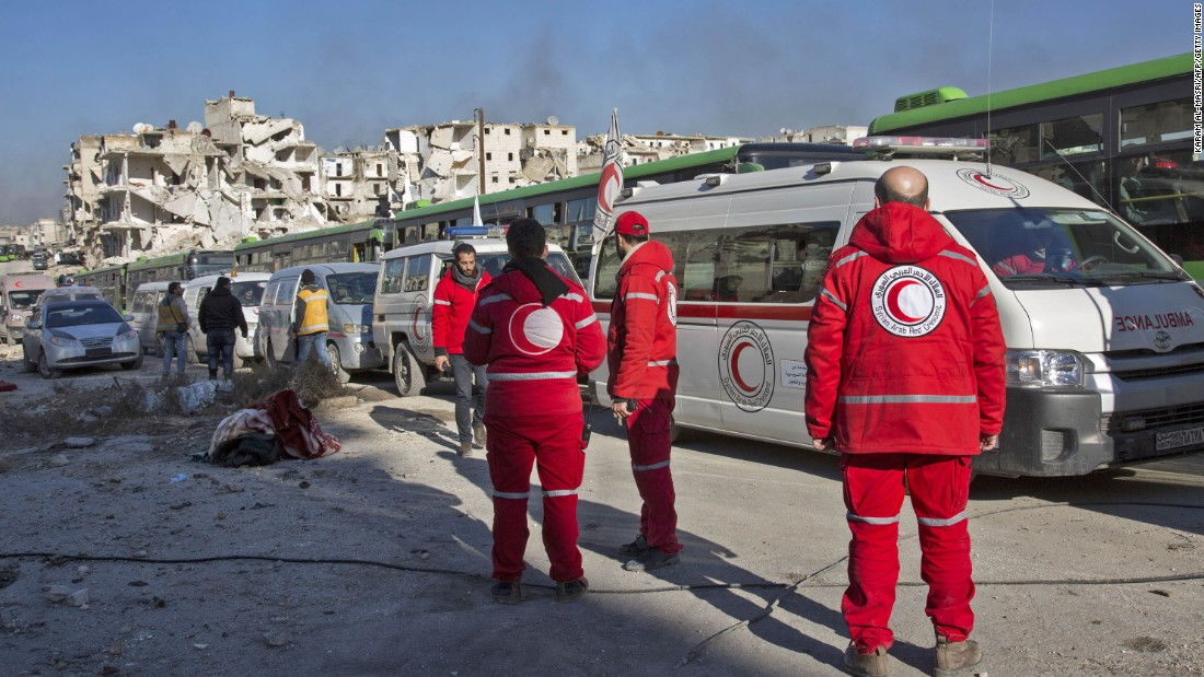 Staff members of the Syrian Red Crescent wait near ambulances as the evacuation operation gets underway on December 15.