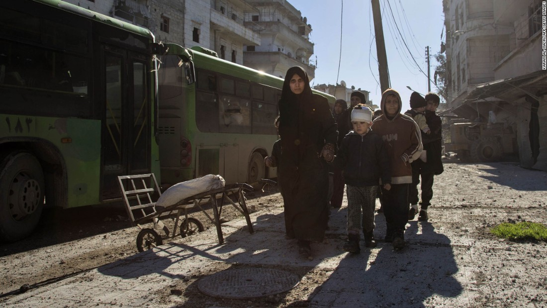 A woman leads family members toward the evacuation buses on December 15.
