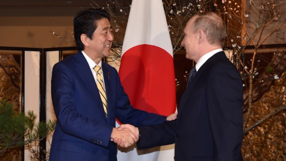 Abe, left, shakes hands with Putin prior to their talks in Nagato on December 15.