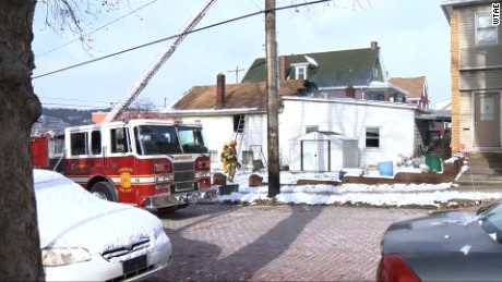 Fire officials survey damage to a house in Ambridge, Pennsylvania, after striking teachers pulled three people out of a fire.
