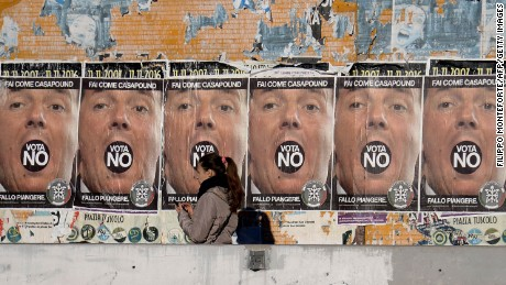 "A woman walks past posters for the far-right CasaPound party, urging a ""No"" vote in Italy's referendum."