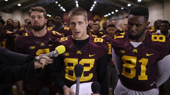 University of Minnesota wide receiver Drew Wolitarsky, flanked by quarterback Mitch Leidner, left, and tight end Duke Anyanwu stands in front of other team members as he reads a statement on behalf of the players in the Nagurski Football Complex in Minneapolis, Minn., Thursday night, Dec. 15, 2016.  The players delivered a defiant rebuke of the university