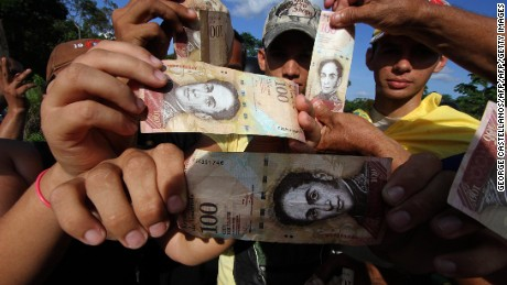 "People hold up 100-Bolivar notes during a protest over lack of cash as the new bank notes have not yet appeared, at the ""Troncal 5"" road in San Cristobal in Venezuela's Tachira state, on December 16, 2016.    Venezuelans lined up to deposit 100-unit banknotes before they turned worthless, but replacement bills had yet to arrive, increasing the cash chaos in the country with the world's highest inflation. Venezuelans are stuck in currency limbo after President Nicolas Maduro ordered the 100-bolivar note -- the largest denomination, currently worth about three US cents -- removed from circulation in 72 hours. / AFP / GEORGE CASTELLANOS        (Photo credit should read GEORGE CASTELLANOS/AFP/Getty Images)"