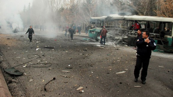 A police officer and people walking next to the wreck of public bus following an explosion on December 17, 2016 in Kayseri, central Turkey.