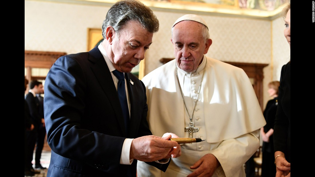 "Colombian President Juan Manuel Santos, left, reads aloud words engraved on a pen as he meets with Pope Francis at the Vatican, Friday, December 16, 2016. The words ""The bullets have written our past, education will write our future"" are engraved on the pen, made from a recycled bullet once used in the civil war between the Colombian government and the Revolutionary Armed Forces of Colombia (FARC). The pen was later used to sign the peace agreements between the parties earlier this year. Santos, who was awarded the 2016 Nobel Peace Prize for his efforts to end the region's longest-running conflict, presented Pope Francis with the pen."