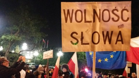 """A demonstrator holds a sign reading """"Freedom of Speech"""" outside the Polish parliament building Friday."""