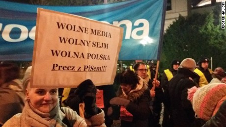 "A woman holds a sign reading ""Free media, free parliament, free Poland"" during Friday's protest outside the legislature."