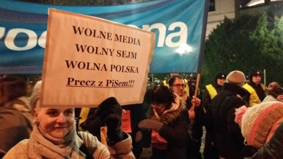 """A woman holds a sign reading """"Free media, free parliament, free Poland"""" during Friday's protest outside the legislature."""