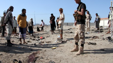 Yemenis gather after a suicide bomber targeted a crowd of soldiers on Sunday.