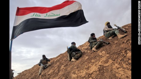 TOPSHOT - Shiite fighters from the Hashed al-Shaabi (Popular Mobilisation) paramilitary units sits under an Iraqi flag as they advance towards the village of Shwah, south of the city of Tal Afar on the western outskirts of Mosul, on December 13, 2016, during an ongoing operation against Islamic State (IS) group jihadists.
