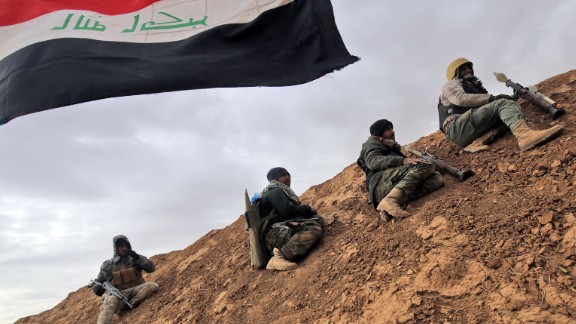TOPSHOT - Shiite fighters from the Hashed al-Shaabi (Popular Mobilisation) paramilitary units sits under an Iraqi flag as they advance towards the village of Shwah, south of the city of Tal Afar on the western outskirts of Mosul, on December 13, 2016, during an ongoing operation against Islamic State (IS) group jihadists.Hashed al-Shaabi paramilitary forces said they retook three more villages southwest of Mosul, completing another phase in operations aimed at cutting the jihadists