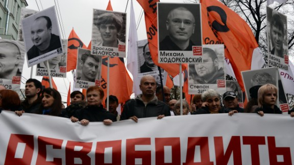 """Thousands of Russians carry placards of political prisoners including Khodorkovsky and a banner reading """"Freedom!"""" during an opposition rally in Moscow in 2013."""
