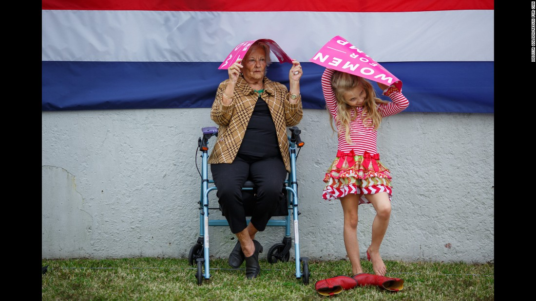 "Mary Nell Moseley and her 8-year-old great granddaughter Lilly Key try to stay dry as they wait for Trump to speak. ""I think he'll be wonderful for women,"" Moseley said. ""I think he's gonna be good for everybody."""