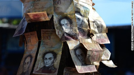 "People tie 100-Bolivar notes to a post during a protest over lack of cash as the new bank notes have not yet appeared, at the ""Troncal 5"" road in San Cristobal in Venezuela's Tachira state, on December 16, 2016.  Venezuelans lined up to deposit 100-unit banknotes before they turned worthless, but replacement bills had yet to arrive, increasing the cash chaos in the country with the world's highest inflation. Venezuelans are stuck in currency limbo after President Nicolas Maduro ordered the 100-bolivar note -- the largest denomination, currently worth about three US cents -- removed from circulation in 72 hours. / AFP / GEORGE CASTELLANOS        (Photo credit should read GEORGE CASTELLANOS/AFP/Getty Images)"