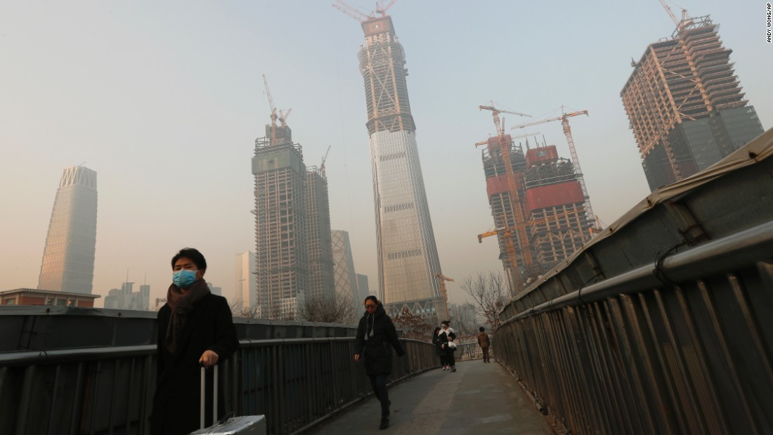 A person wears a mask while crossing a bridge in Beijing on Monday, December 19. A gray haze of smog descended on Northeast China over the weekend, and China has issued a red alert for 23 cities.