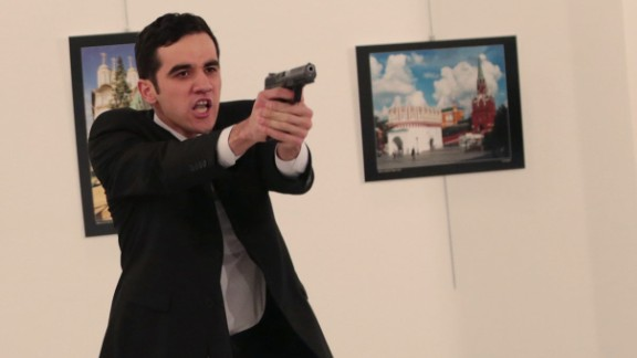 An unnamed gunman gestures after shooting the Russian Ambassador to Turkey, Andrei Karlov, at a photo gallery in Ankara, Turkey, Monday, Dec. 19, 2016. The Russian foreign ministry spokeswoman said he was hospitalized with a gunshot wound. (AP Photo/Burhan Ozbilici)