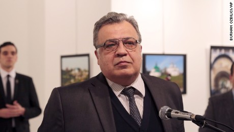 Karlov moments before he was gunned down while speaking at a new photo exhibition in Ankara, Turkey. The gunman is seen at rear on the left.