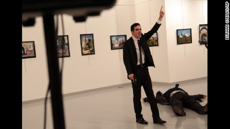 A man gestures near to the body of a man at a photo gallery in Ankara, Turkey, Monday, Dec. 19, 2016. An Associated Press photographer says a gunman has fired shots at the Russian ambassador to Turkey. The ambassador's condition wasn't immediately known. (AP Photo/Burhan Ozbilici)