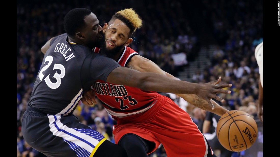 Portland's Allen Crabbe is fouled by Golden State's Draymond Green during an NBA game in Oakland, California, on Saturday, December 17.