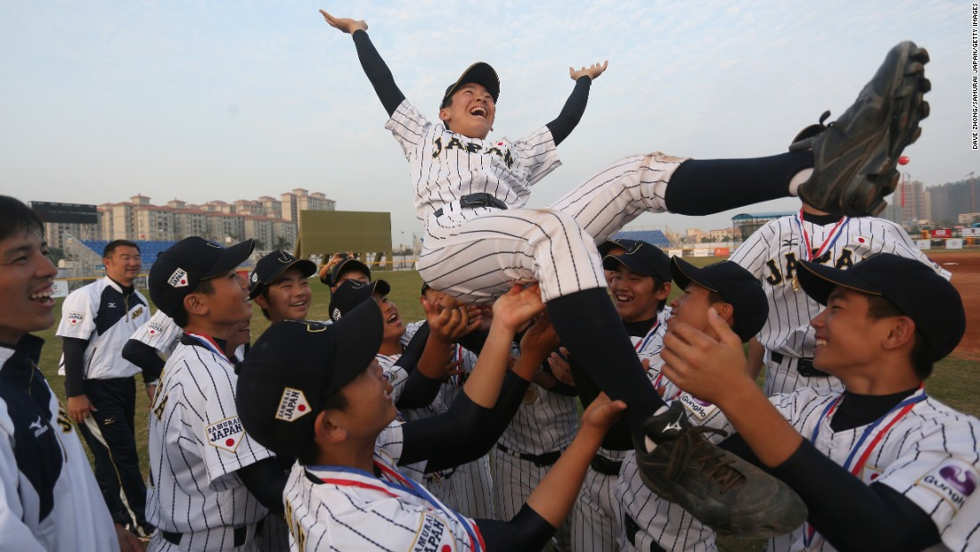 Japanese players hold up Hosiko Temma after defeating Korea to win an under-12 baseball tournament in Zhongshan, China, on Tuesday, December 13.