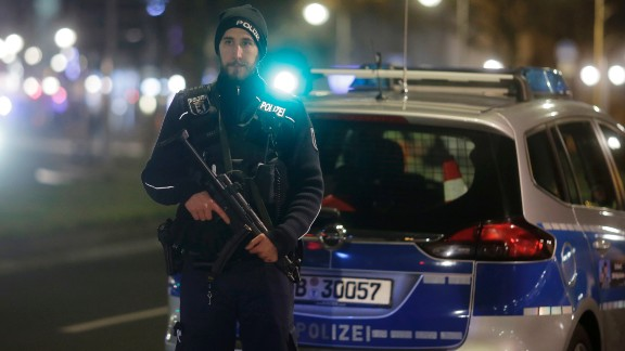 An armed police officer stands near the scene.