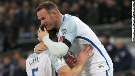 England captain Wayne Rooney celebrates after defender Gary Cahill (left) scores against Scotland.