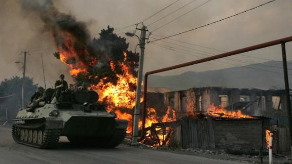 A Russian armoured vehicle passes a house set on fire by seperatist militia during the conflict between  Georgia and Russia, on August 18, 2008.