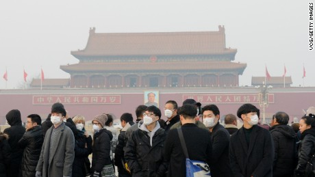 BEIJING, CHINA - DECEMBER 18:  Tourists wearing masks visit the Tiananmen Square on December 18, 2016 in Beijing, China. At least 24 cities in North China issued red alerts on Friday as heavy smog will shroud the country's northern regions in the following two days.  (Photo by VCG/VCG via Getty Images)